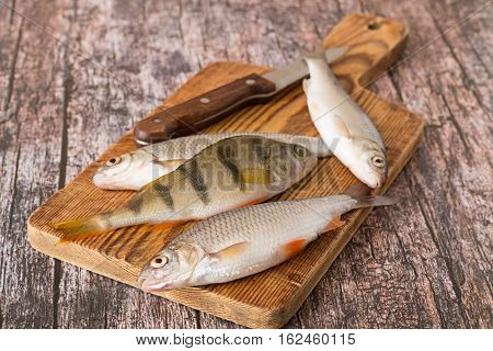 Fresh river fish, perch and roach, and knife on a cutting board on an old wooden table.