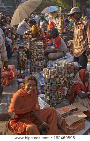 AHMADABAD, INDIA - OCTOBER 31, 2007: Woman in colourful sari selling crockery at a street market in the city of Ahmadabad, Gujarat, India