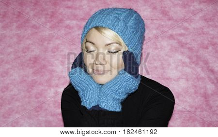 Portrait of a girl in blue knitted cap and mittens kroplin up on a pink background. Snow maiden Dreams