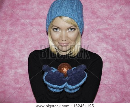 Portrait of a girl in blue knitted cap and mittens kroplin up on a pink background. Snow maiden with Christmas toys