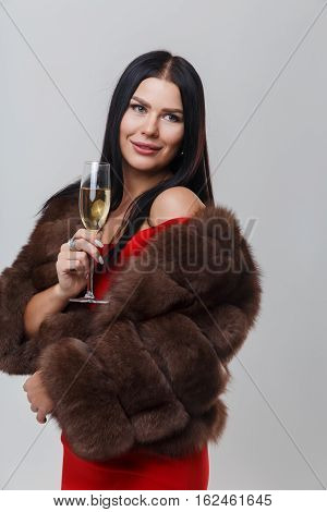 Portrait of woman in mink coat and red dress with glass of champagne on empty gray background