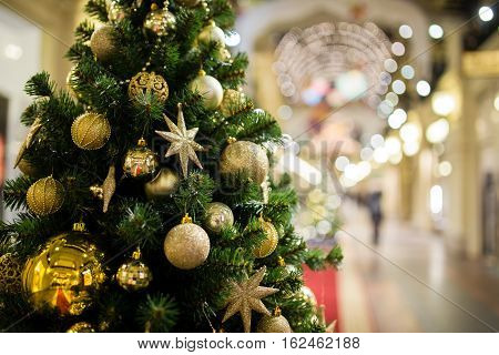 Holiday tree with golden decorations on blurred background shopping center
