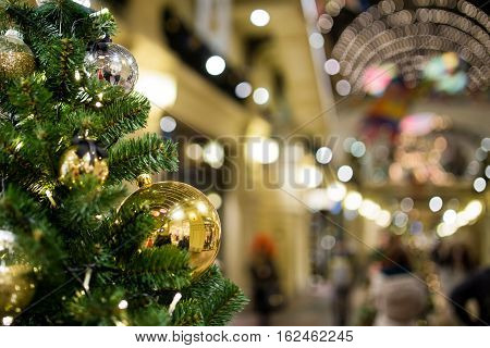 Festive pine with Christmas toys on background of shopping center