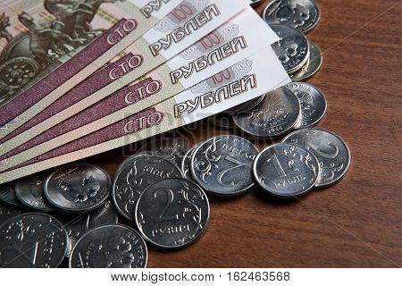 Russia's hundred-ruble banknotes and coins on the table closeup