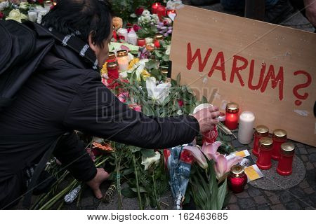 Berlin Germany - december 20, 2016: Man put candle and flowers at the Christmas Market in Berlin the day a truck drove into a crowd of people.