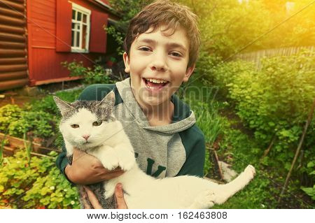 preteen handsome boy with siberian tom cat close up country summer portrait with cottage house on the background