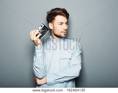 Hipster fashion photographer man holding retro camera over grey wall