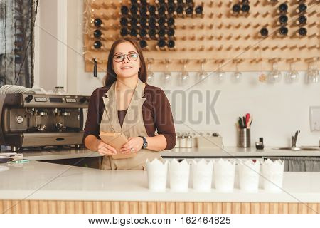 Young smiling woman standing with cookbook in her kitchen