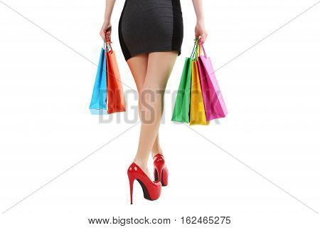 Female Legs With Red High Heels And Shopping Bags On A White Background