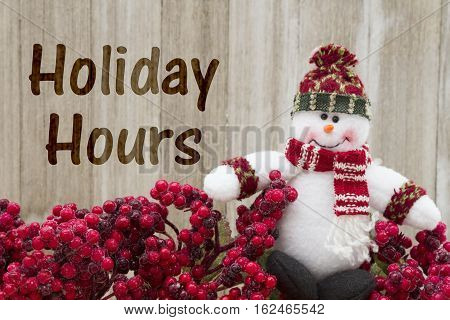 Old fashion Christmas store message Frost covered red holly berries with a snowman on weathered wood background with text Holiday Hours