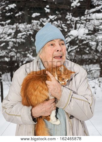 Portrait of an old Granny with a ginger cat on his hands. Winter snow