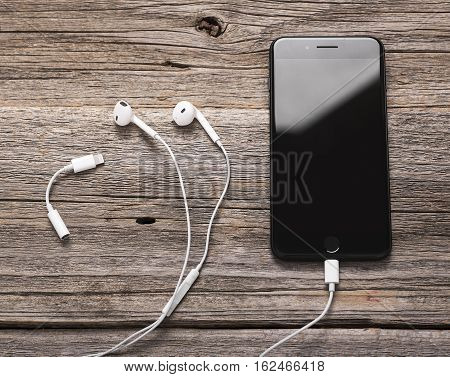 UZHGOROD, UKRAINE - DECEMBER 20, 2016: New black iPhone 7 Plus with headphones from the company Apple, and a new adapter with lightning to mini jack 3.5 mm., on wooden background.