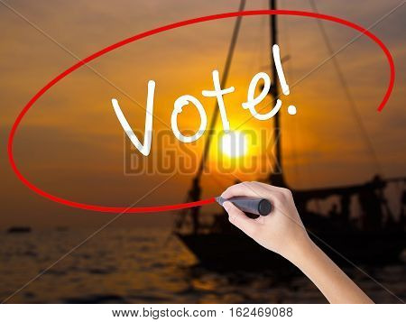 Woman Hand Writing Vote! With A Marker Over Transparent Board