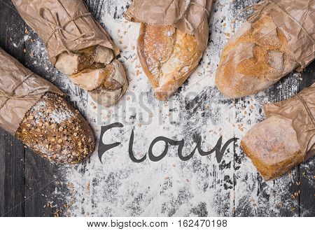 Baking and cooking concept background. Lots of different bread sorts, wrapped in craft paper top view with flour text on copy space in middle on wooden table, sprinkled with flour. Soft toning