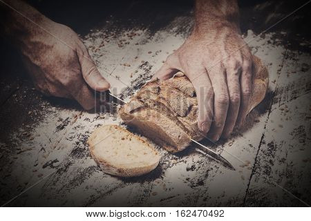 Baking and cooking concept background. Hands of baker cutting bread loaf with knife on rustic wooden table sprinkled with flour. Stained dirty hands of baker. Dark filtered