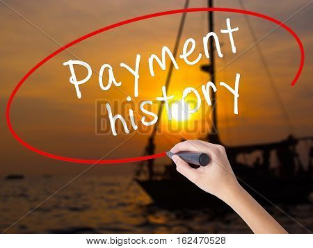 Woman Hand Writing Payment History With A Marker Over Transparent Board
