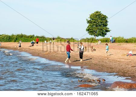 PETERHOF, SAINT - PETERSBURG, RUSSIA - JULY 14, 2016: Alexandria Park. People rest on the beach of The Gulf of Finland. Park is last summer residence of the Russian Emperors from 1830 until 1917