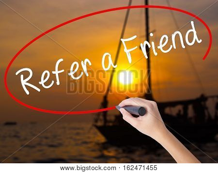 Woman Hand Writing Refer A Friend  With A Marker Over Transparent Board