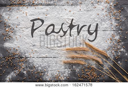 Baking class or recipe concept on dark background, sprinkled wheat flour with pastry text copy space. Baking preparation, top view on wooden board or table. Cooking dough or pastry.