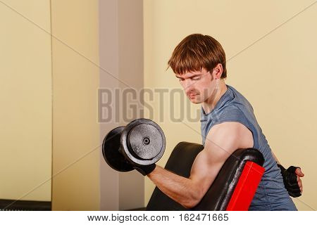 Man doing exercise for biceps with dumbbell. Working with free weights. Healthy lifestyle concept. Fitness.