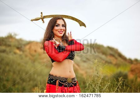 Oriental Beauty dance with a sword. Tribal style. Nice girl in national dress dancing in the open air. Nomads. Sword on the head girl