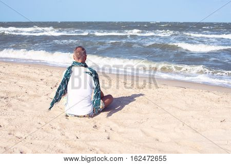 Man In Scarf Sitting On The Beach