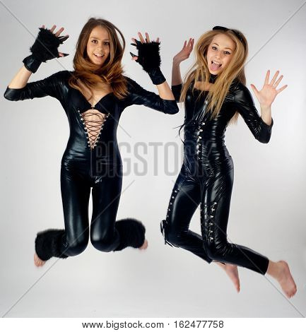 Two attractive young woman in cat costumes jumping over white background