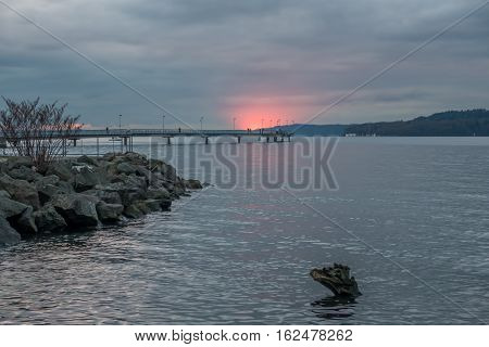 A section of the horizon flares up in red as the sun sets behind the clouds in Des Moines Washington.