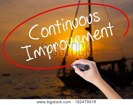 Woman Hand Writing Continuous Improvement With A Marker Over Transparent Board