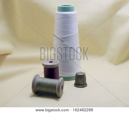 Spool of treads thimble and a needle on textile background. Vintage