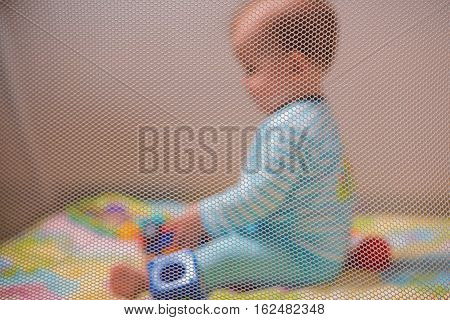 Cute kid playing with toys in a playpen