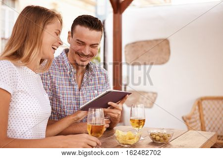 Laughing Couple With Touchpad And Beers