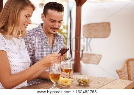 Interested Young Couple Looking At Cellphone