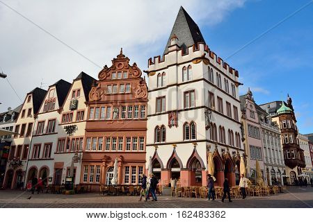 Trier, Germany - April 26, 2016. Street view in Trier, with Renaissance historic buildings Steipe with white facade in the center and Rotes Haus Red House, to the left , with commercial properties and people.