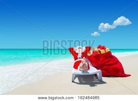 Santa Claus with Christmas sack full of gifts with bows relax on sunlounger barefooted at perfect sandy ocean beach. Happy New Year and merry xmas travel destinations for tropical vacations concept.