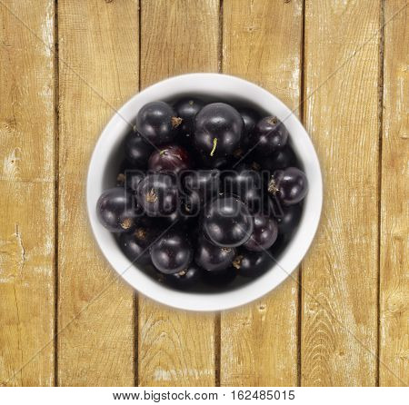 Black currants in a white ceramic bowl. Top view. Ripe and tasty currants on a wooden background.