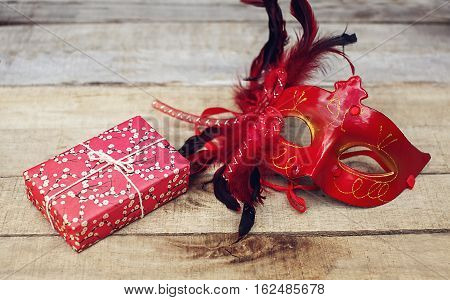 Carnival mask and gift box on wooden background. Christmas festive concept.