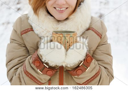Smiling Young Woman In Winter Coat And White Fluffy Mittens Holds Pottery Cup In Her Hands At Snowy