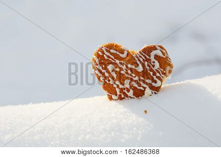 Beautiful Biscuit Heart Shaped Cookie With Icing Stands In Snow.