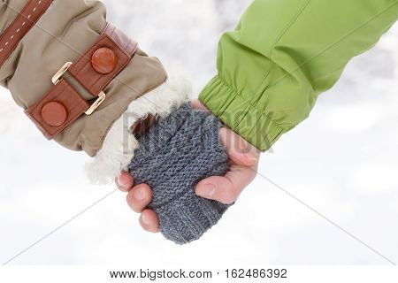 Female hand in winter coat with white fur and grey knitted mittens and male hand in green sports jacket holding together at snowy background.