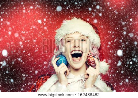 Cheerful pretty girl or cute beautiful woman female model in wig santa hat and suit with Christmas or new year baubles winks on red background under snow and snowflakes