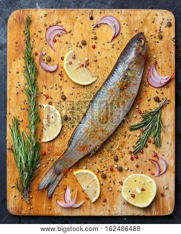 Fresh Grey Mullet Fish Lies On Light Wooden Cutting Board With Lemon Segments, Onion Slices, Rosemar