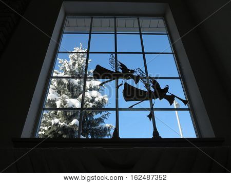 Fresh snow on pine tree  with angel decorations  looking  out from the window
