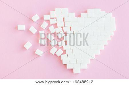 Broken heart made of sugar cubes. Rupture of relations. Sugar kills