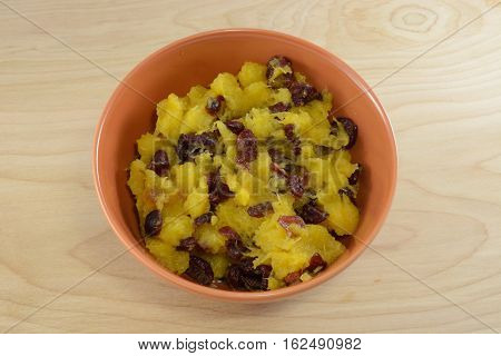 Acorn squash with dried cranberries in orange bowl
