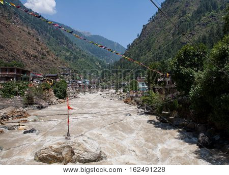View of the rapid river Parvati and Sacred prayer flags near Sikhs temple and a Gurudwara, Manikaran, Himachal Pradesh, Northern India.