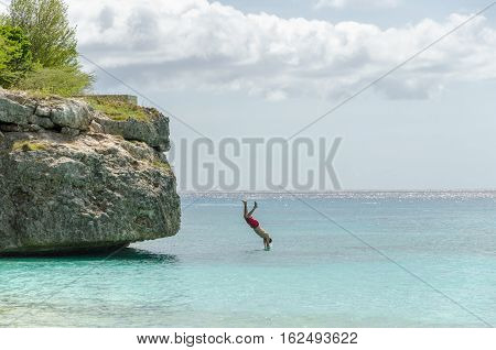 Tourist Jumping From The Rock At The Grand Knip Beach