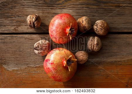 On wooden tanle are two pomegranate and walnuts. The picture is removed from the top. Nuts ripe. Autumn harvest. Pomegranates are large and ripe. Peel pinkish berries with red spots. Aged wooden surface with cracks. The composition is removed in the stree