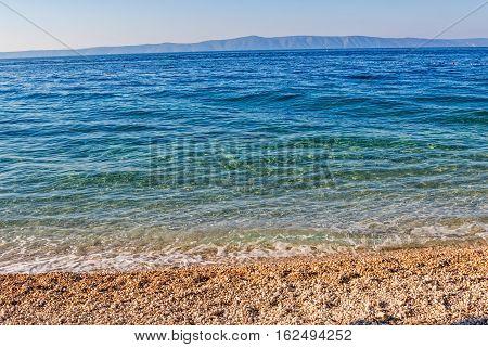 Beautiful sunshine on the clear blue sea, Tucepi town beach in Croatia Europe.