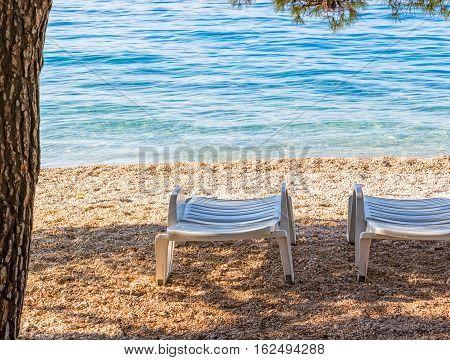Deck chairs on the beach in Tucepi Croatia.